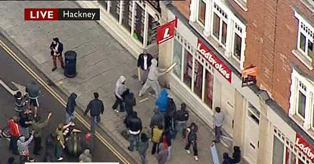 rioter smashes shop window