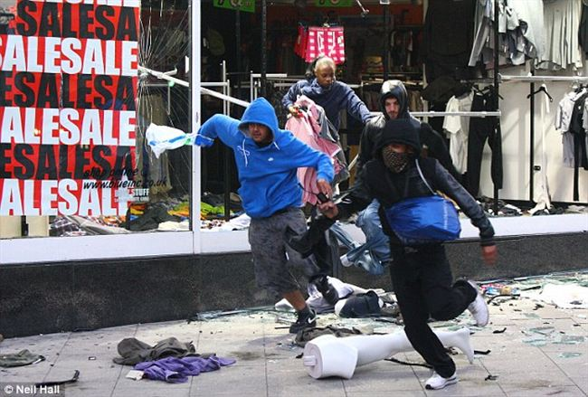 the runLooters burst through the window shop Peckham high street carrying their spoils